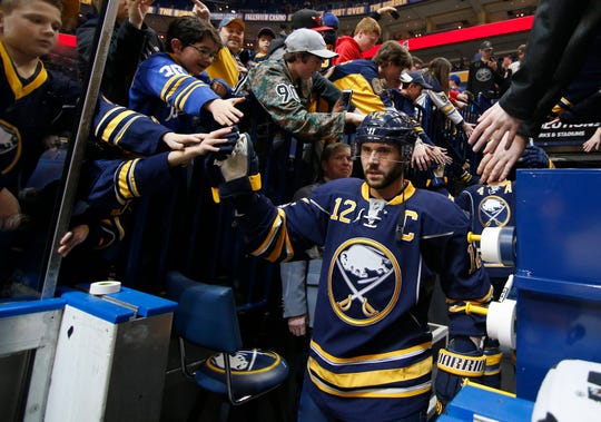 Buffalo Sabres right wing Brian Gionta greets fans while walking to the ice prior to his 1,000th career NHL game against the Florida Panthers at KeyBank Center in Buffalo.