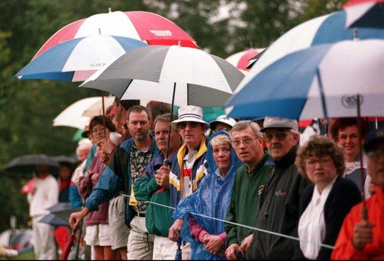 Spectators line the 17th green braving the rain on Wednesday, Sept. 20, 1995.