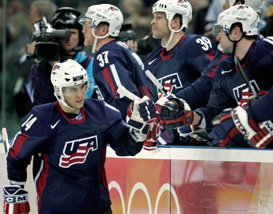The United States' Brian Gionta (14) is congratulated at the bench after scoring against Latvia during a 2006 Winter Olympics men's ice hockey game Wednesday, Feb. 15, 2006, in Turin, Italy.