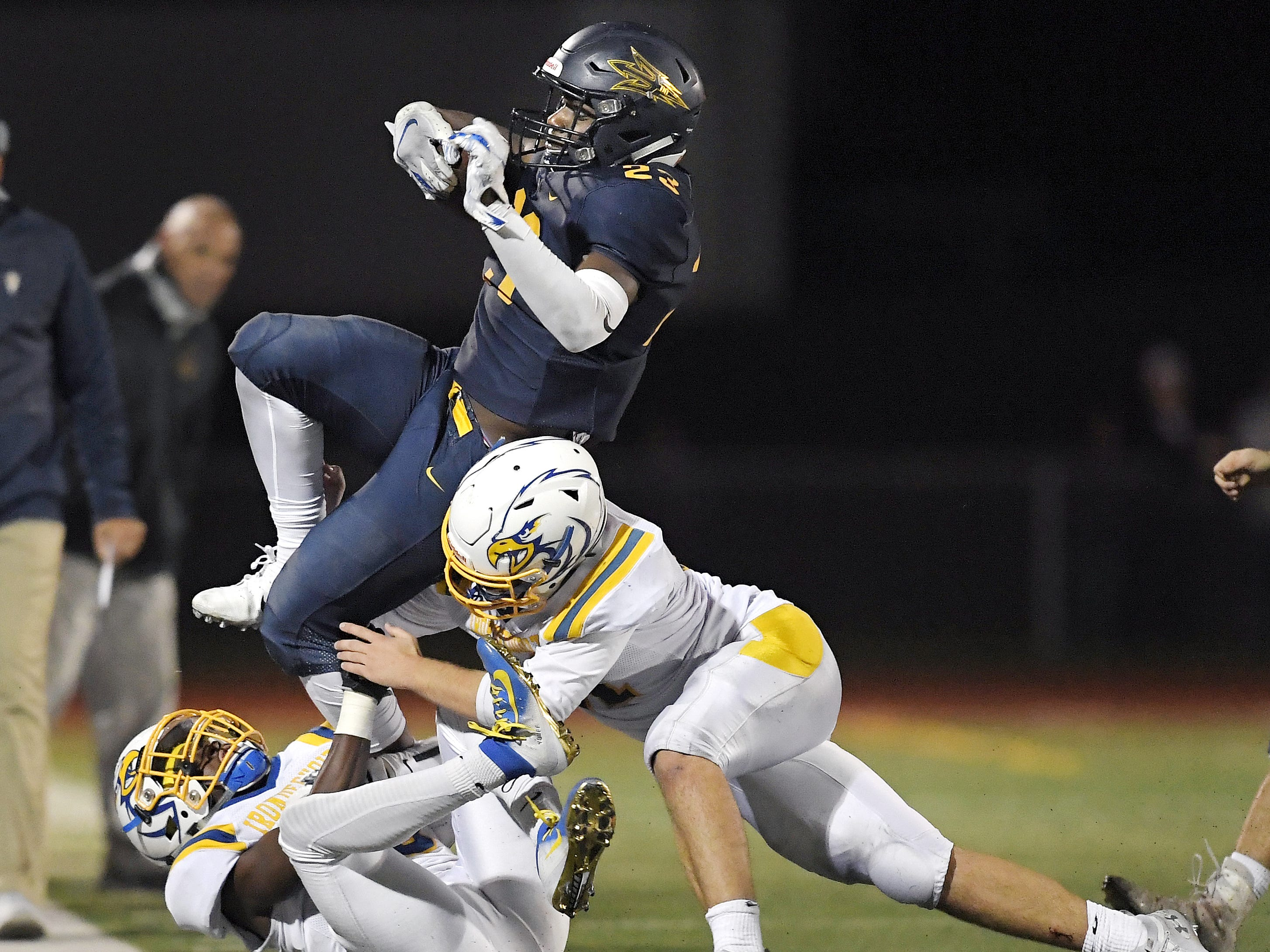 Victor's Rushawn Baker, top, is driven out of bounds by Irondequoit's Purcell Brown, left, and Liam Smith  during a regular season game played at Victor High School, Sunday, Sept. 23, 2018. Irondequoit beat Victor 28-21.