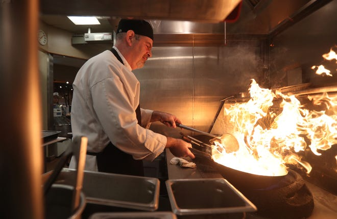 Carl Suero, a cook in the Asian kitchen, prepares meals for the lunch crowd at the Caulkins Road Wegmans.