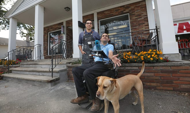 Victor Burgos, left, a hairstylist at Joe's Upscale Barber Shop, with his new customer Devin Hamilton outside the barber shop where Victor cut Devin's hair.  Joining the pair is Devin's service dog, Taco.