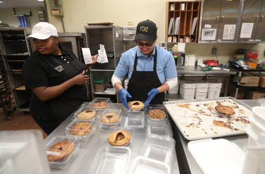 Lucrectia  Johnson, left, and Jo Stewart work in the bakery at the Caulkins Road Wegmans. Wegmans attributes its long history of success to treating employees well.