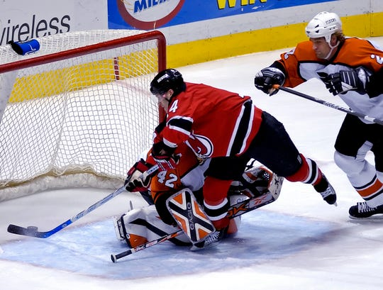 New Jersey Devils' Brian Gionta (14) scores a goal against Philadelphia Flyers goaltender Robert Esche as Flyers' Derian Hatcher, right, looks on during first period  NHL hockey Sunday, April 16, 2006, in East Rutherford, N.J. It was Gionta's 46th goal, tying the Devils' season mark set by Pat Verbeek in the 1987-88 season. The Devils won, 5-1.