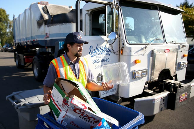 Suburban driver Shane Kuenzi sorts through a recycling bin in northeast Salem on Monday, Sep. 24, 2018. Residents who fail to follow Marion County's strict new recycling rules are beginning to be fined.