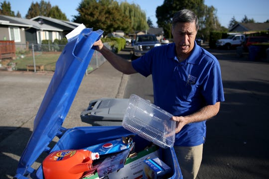 Art Kuenzi, owner of Suburban Garbage, sorts through bins in northeast Salem to show how some residents are recycling improperly on Monday, Sept. 24, 2018. Those residents could face $15 fines.