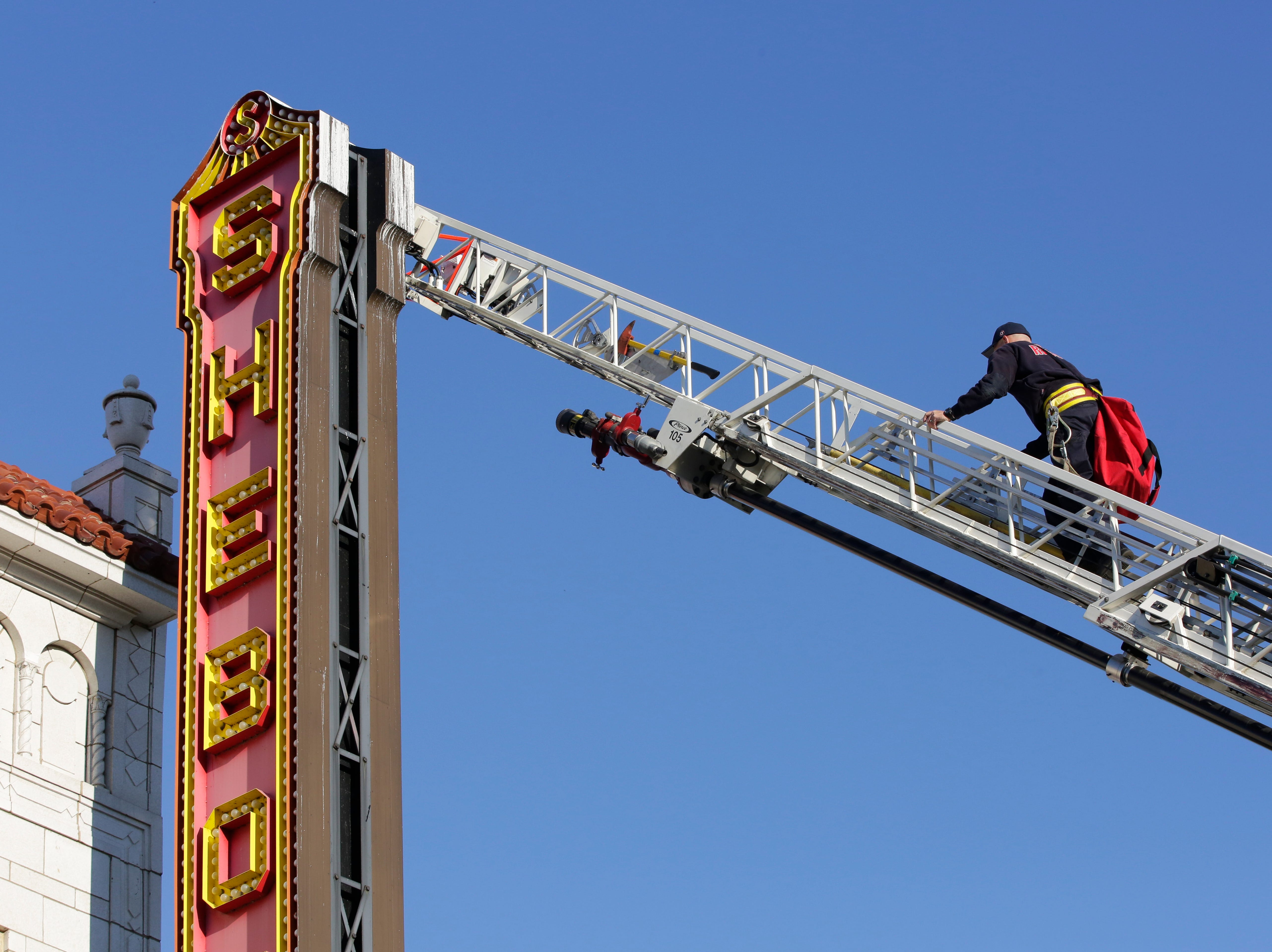 A City of Sheboygan Firefighter climbs up the ladder boom on his way to clean and install new LED lamps on the Stefanie H. Weill Center for the Performing Arts Center, Sunday, September 23, 2018, in Sheboygan, Wis. The marquee has some 3000 bulbs that will be going to LED.