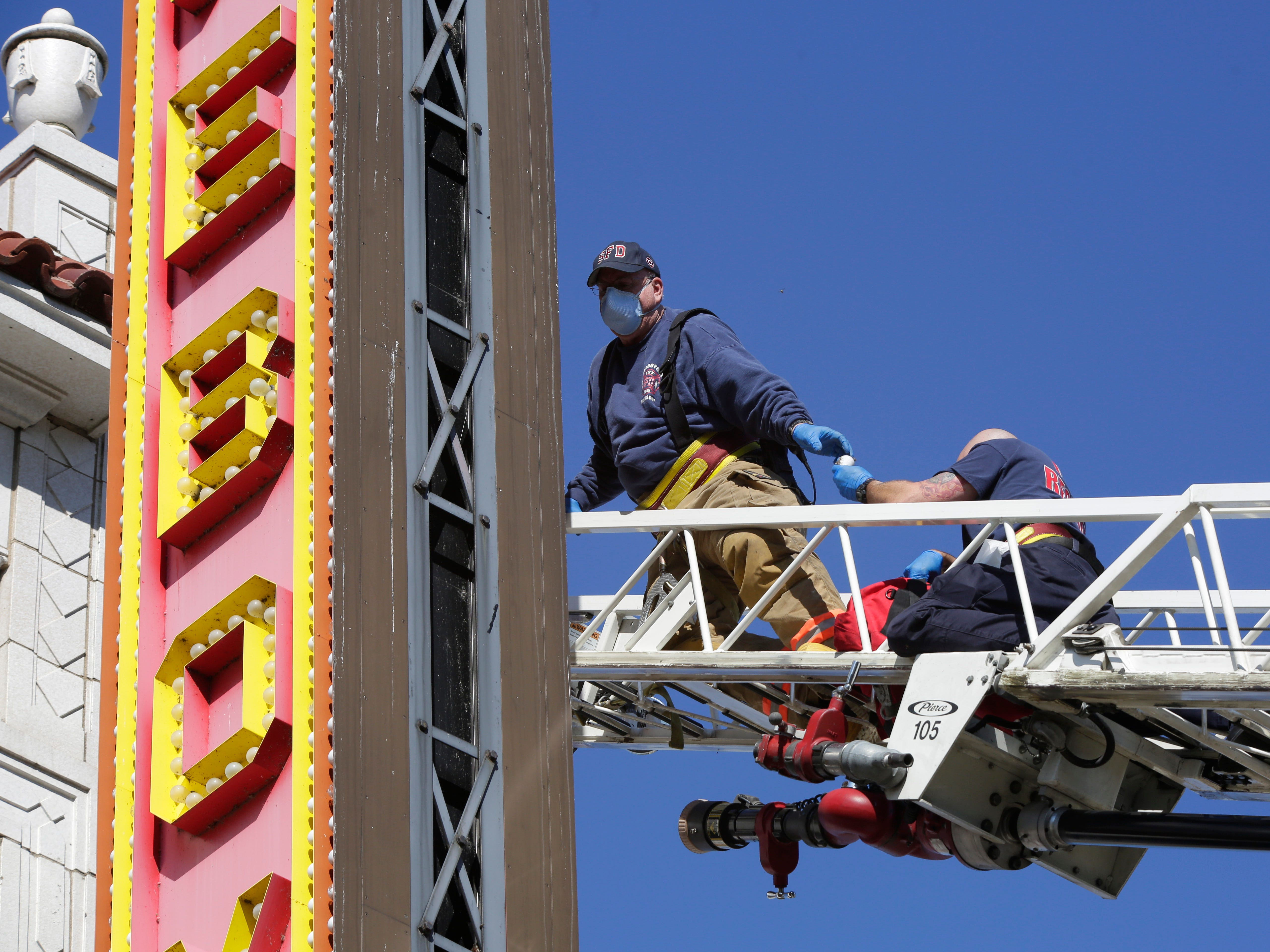 City of Sheboygan firefighters install new LED bulbs at the Stefanie H. Weill Center for the Performing Arts, Sunday, September 23, 2018, in Sheboygan, Wis. The marquee has some 3000 bulbs that will be going to LED.