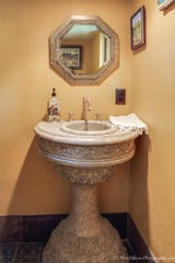 The powder room tucked under the stairs features an ornate pedestal carved sink and greenencaustic reclaimed tiles circa 1840 from Europe.