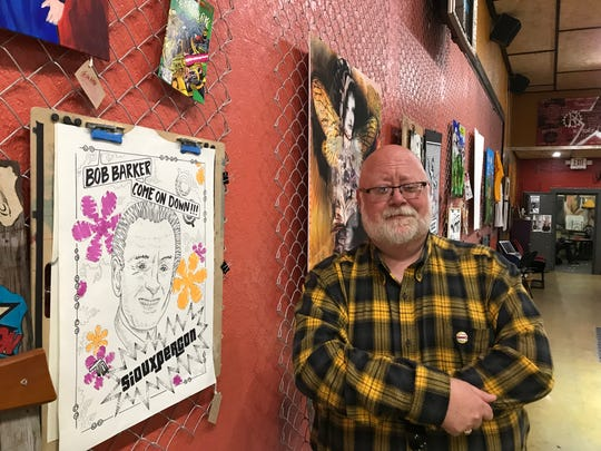 Shane Gerlach, chairman of SiouxperCon, stands  by a display of  pages from a special-edition comic book made for SiouxperCon, on display in Vishnu Bunny Tattoos  in downtown Sioux Falls.