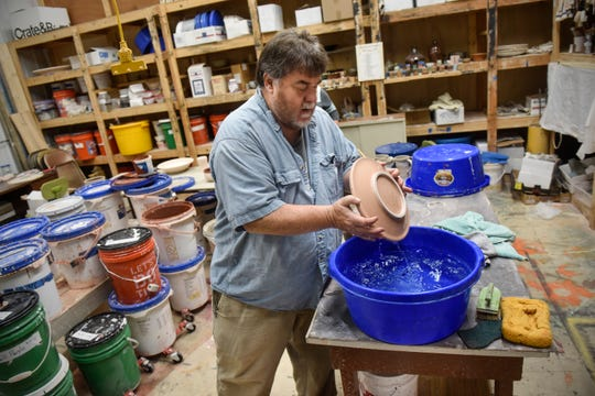 David Glenn dips a ceramic plate into water before glazing it Wednesday, Sept. 19, at the Paramount Center for the Arts technical building in Waite Park. Glenn has been a part of the Millstream Arts Festival for years.