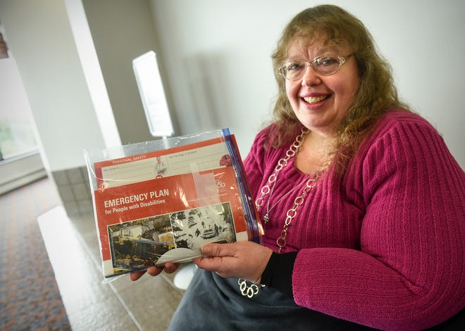 Kim Pettman holds a packet of materials on emergency planning for people with disabilities Monday, Sept. 24, in St. Cloud.
