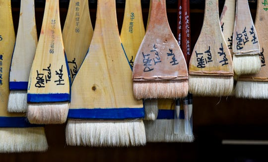 Brushes used used to work with glaze on ceramics line a shelf at the Paramount Center for the Arts technical building Wednesday, Sept. 19, in Waite Park.