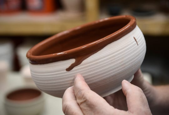 David Glenn examines a bowl after dipping it in glaze Wednesday, Sept. 19, at the Paramount Center for the Arts technical building in Waite Park.