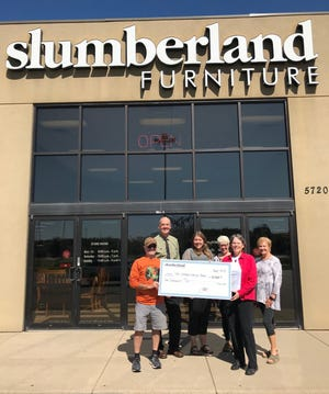 Mary Hesch (second from right), local owner of Slumberland Furniture in Stevens Point, donates $10,000 to the Green Circle Trail.