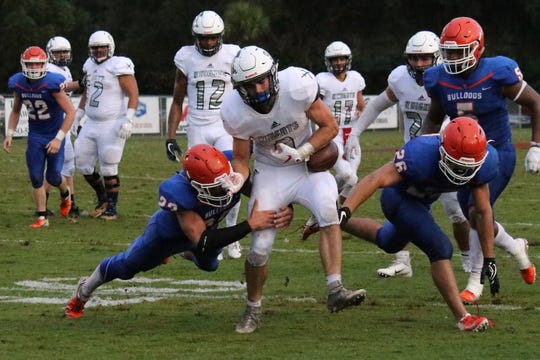 Taylor County's Max Kallschmidt tries to make a tackle on Clearwater Academy International's quarterback, who fumbles but recovers.