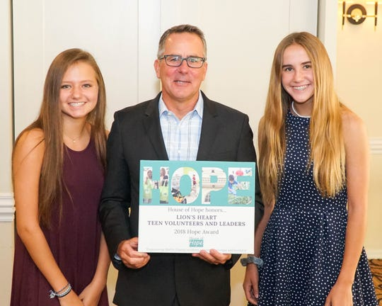 House of Hope Board Chairman Stephen Schramm, center, gives Keira Hodum and Hannah Moss a 2018 Hope Award honoring the Lion's Heart Teen Volunteers for their consistent volunteer efforts for House of Hope throughout the year.