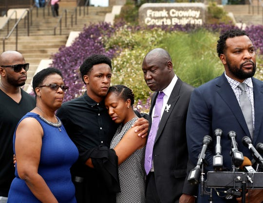 Brandt Jean, center left, brother of shooting victim Botham Jean, hugs his sister Allisa Charles-Findley, during a news conference outside the Frank Crowley Courts Building on Monday, Sept. 10, 2018, in Dallas, about the shooting of Botham Jean by Dallas police Officer Amber Guyger on Sept. 6, 2018. He was joined by his mother, Allison Jean, second from left, and attorney Benjamin Crump, second from right, as attorney Lee Merritt, right, speaks to the media.