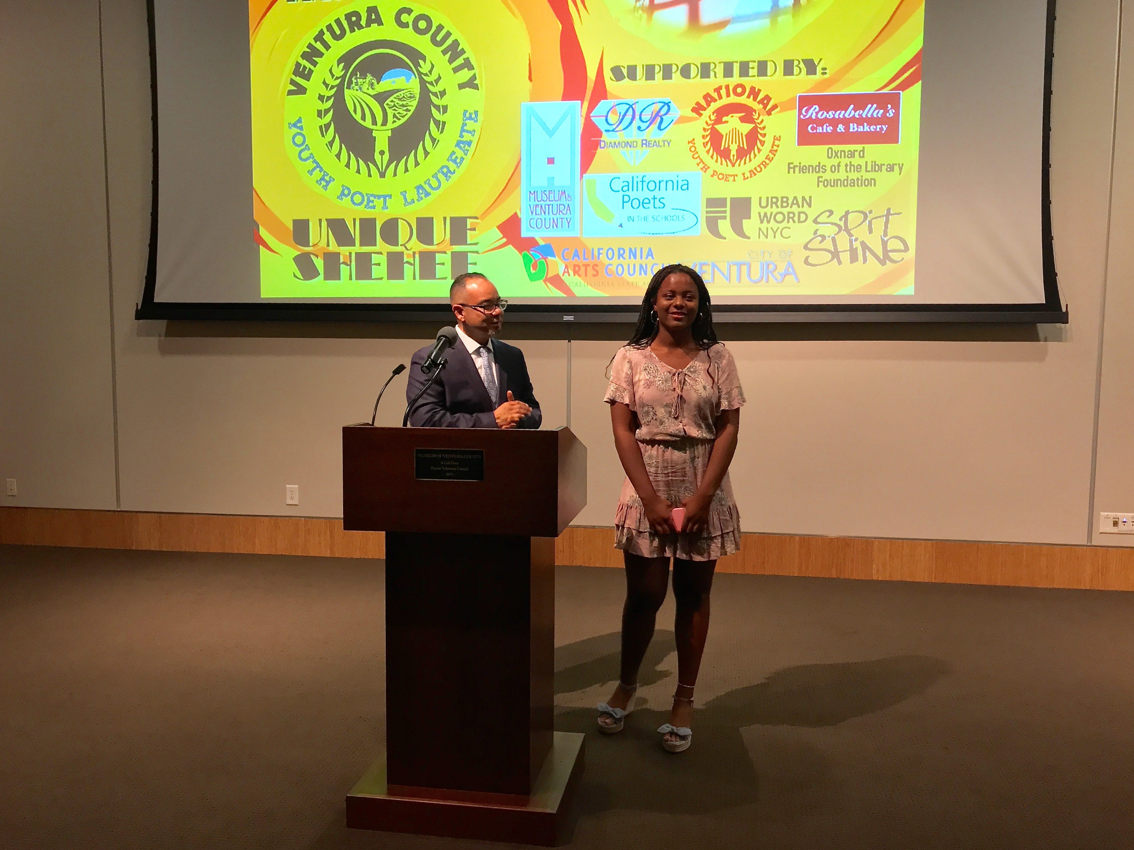 Fernando Salinas, literary arts programs coordinator for the Ventura County Arts Council, congratulates Unique Shehee on becoming the first Ventura County youth poet laureate.