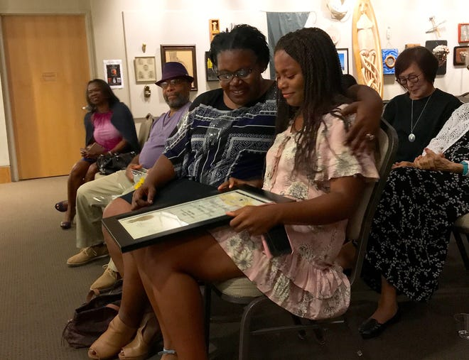 Unique Shehee and her foster mom, Leticia Woodruff, look together at a certificate of recognition Unique received for becoming the first Ventura County youth poet laureate.