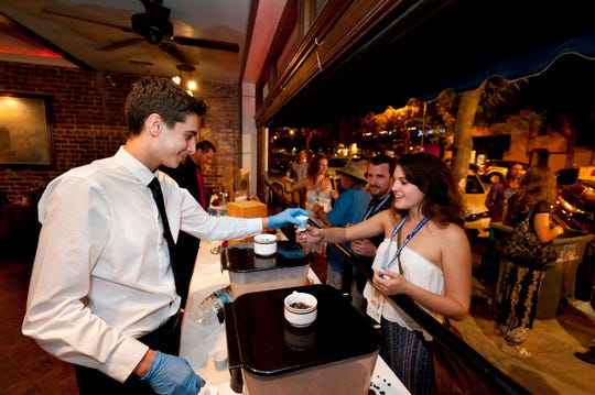 Andre Vaccaro, left, serves iced cappuccino at Little Italy to Hannah Sertich and Marc Amaro during Taste of Downtown Visalia on Tuesday, October 7, 2014.
