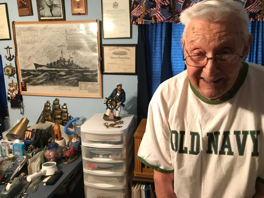 Robert Almquist in his upstairs study, which is filled with memorabilia about his time at sea, including a poster of the USS Oakland signed by many who served on her.