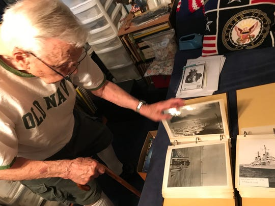 Robert Almquist pages through a photo album filled with pictures of the USS Oakland.