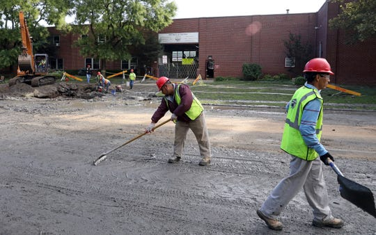 Workers clean up after a water main break on Nepperhan Avenue near Odell Avenue in Yonkers on Sept. 24, 2018.