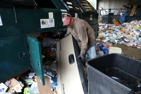 Gary Evans takes a truck tailgate out of a recycling trailer at the Muskingum County Recycling Center on Monday. Employees at the center check incoming recyclables for trash before sending it on to a larger plant in Akron.