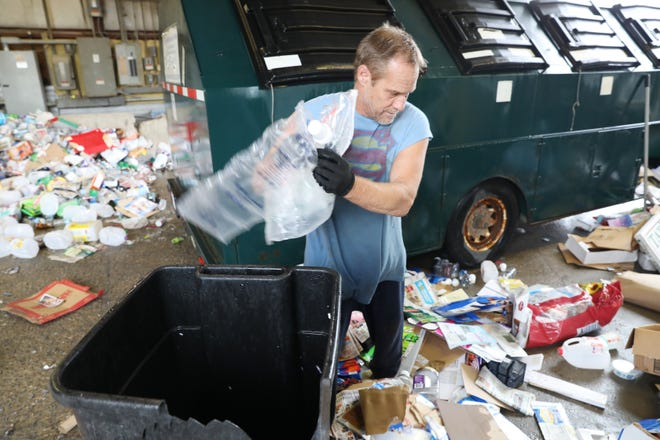John Bates throws out non-recyclable plastics while emptying a recycling trailer at the Muskingum County Recycling Center