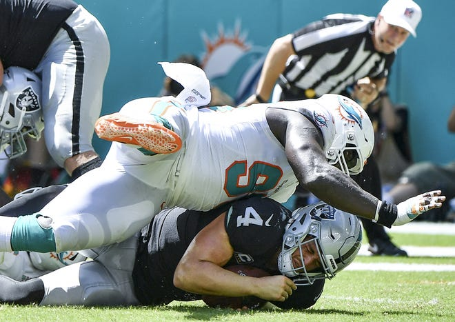 William Hayes #95 of the Miami Dolphins sacks Derek Carr #4 of the Oakland Raiders during the second quarter at Hard Rock Stadium on September 23, 2018 in Miami, Florida.