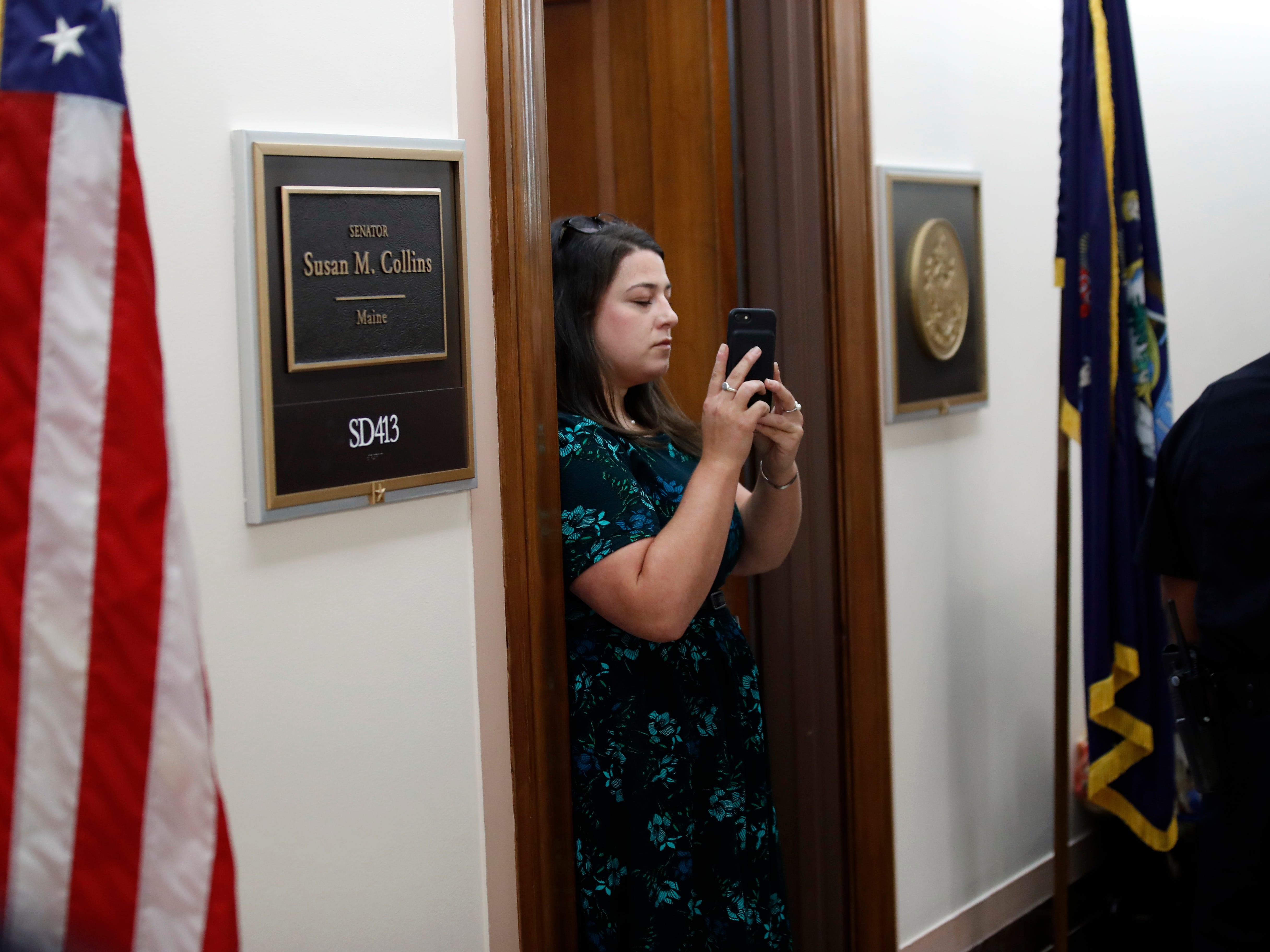 A staff member records protesters against Judge Brett Kavanaugh as Capitol Hill Police officers make arrests outside the office of Sen. Susan Collins, R-Maine, on Capitol Hill, Monday, Sept. 24, 2018 in Washington. A second allegation of sexual misconduct has emerged against Judge Brett Kavanaugh, a development that has further imperiled his nomination to the Supreme Court, forced the White House and Senate Republicans onto the defensive and fueled calls from Democrats to postpone further action on his confirmation. President Donald Trump is so far standing by his nominee. (AP Photo/Alex Brandon) ORG XMIT: DCAB106