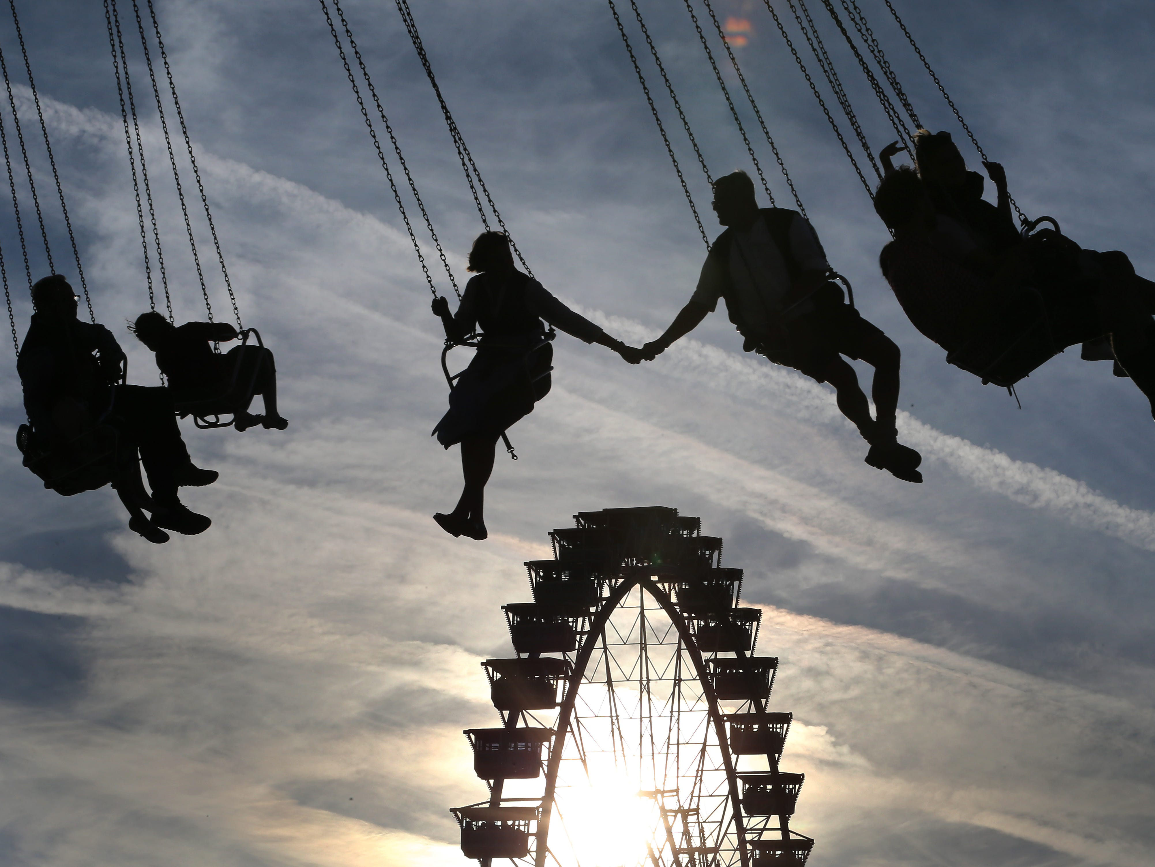 A couple hold hands as they ride a merry-go-round at the Theresienwiese fair ground of the Oktoberfest beer festival in Munich, southern Germany, on Sept. 22, 2018.