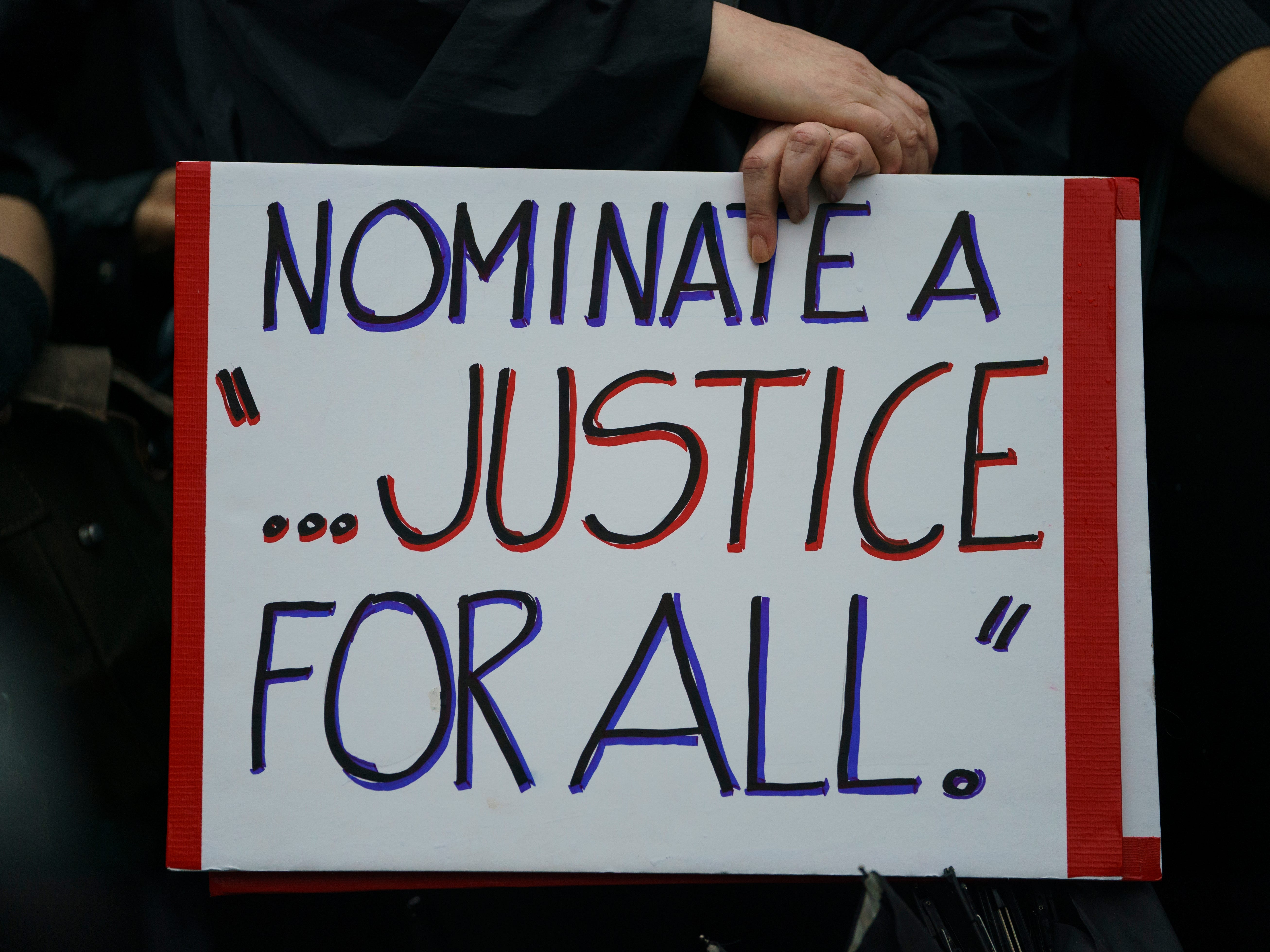 "A protester holds a sign that reads ""Nominate A ...Justice For All"" in front of the Supreme Court on Capitol Hill in Washington, Monday, Sept. 24, 2018. A second allegation of sexual misconduct has emerged against Judge Brett Kavanaugh, a development that has further imperiled his nomination to the Supreme Court, forced the White House and Senate Republicans onto the defensive and fueled calls from Democrats to postpone further action on his confirmation. President Donald Trump is so far standing by his nominee. (AP Photo/Carolyn Kaster) ORG XMIT: DCCK119"