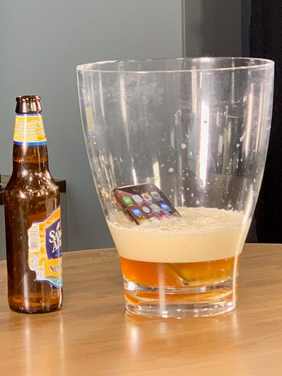 A thirsty iPhone XS drinks beer.