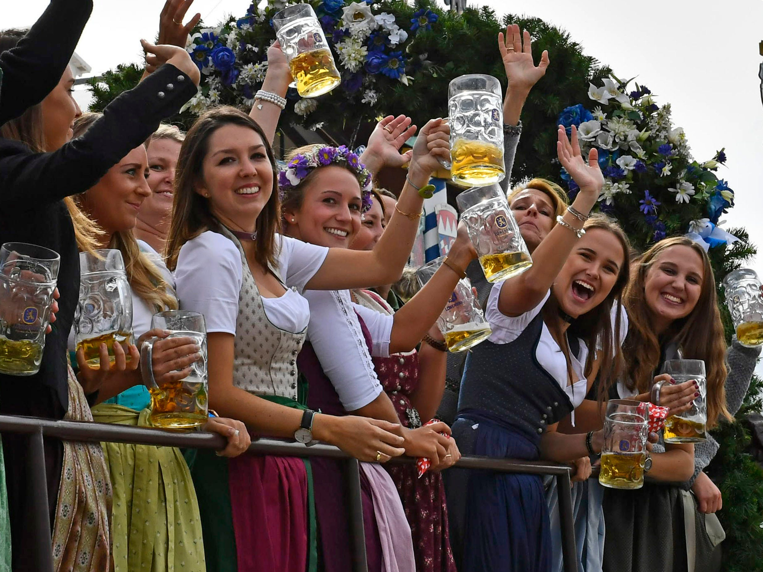 People lift beer mugs during a parade as part of the opening of the 185th 'Oktoberfest' beer festival in Munich, Germany on Saturday, Sept. 22, 2018.