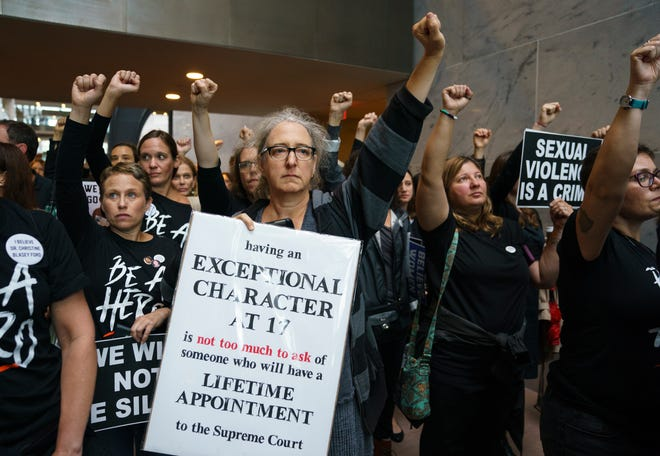 Protesters opposed to President Donald Trump's embattled Supreme Court nominee, Brett Kavanaugh stand quietly with fists raised in Hart Senate Office Building on Capitol Hill in Washington, Monday, Sept. 24, 2018. A second allegation of sexual misconduct has emerged against Judge Brett Kavanaugh, a development that has further imperiled his nomination to the Supreme Court, forced the White House and Senate Republicans onto the defensive and fueled calls from Democrats to postpone further action on his confirmation. President Donald Trump is so far standing by his nominee. (AP Photo/Carolyn Kaster) ORG XMIT: DCCK131