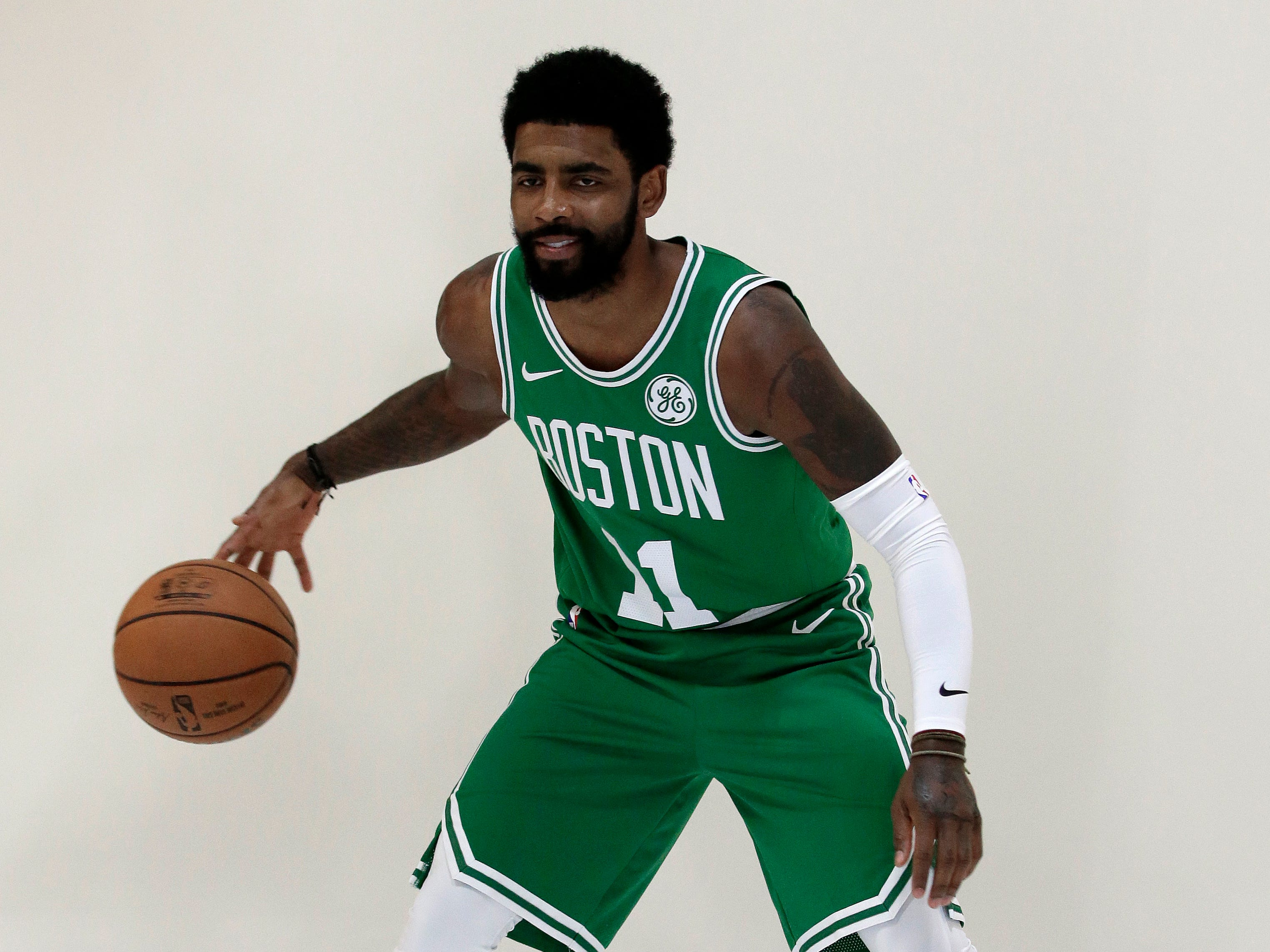 Boston Celtics guard Kyrie Irving dribbles the ball during a photo shoot.