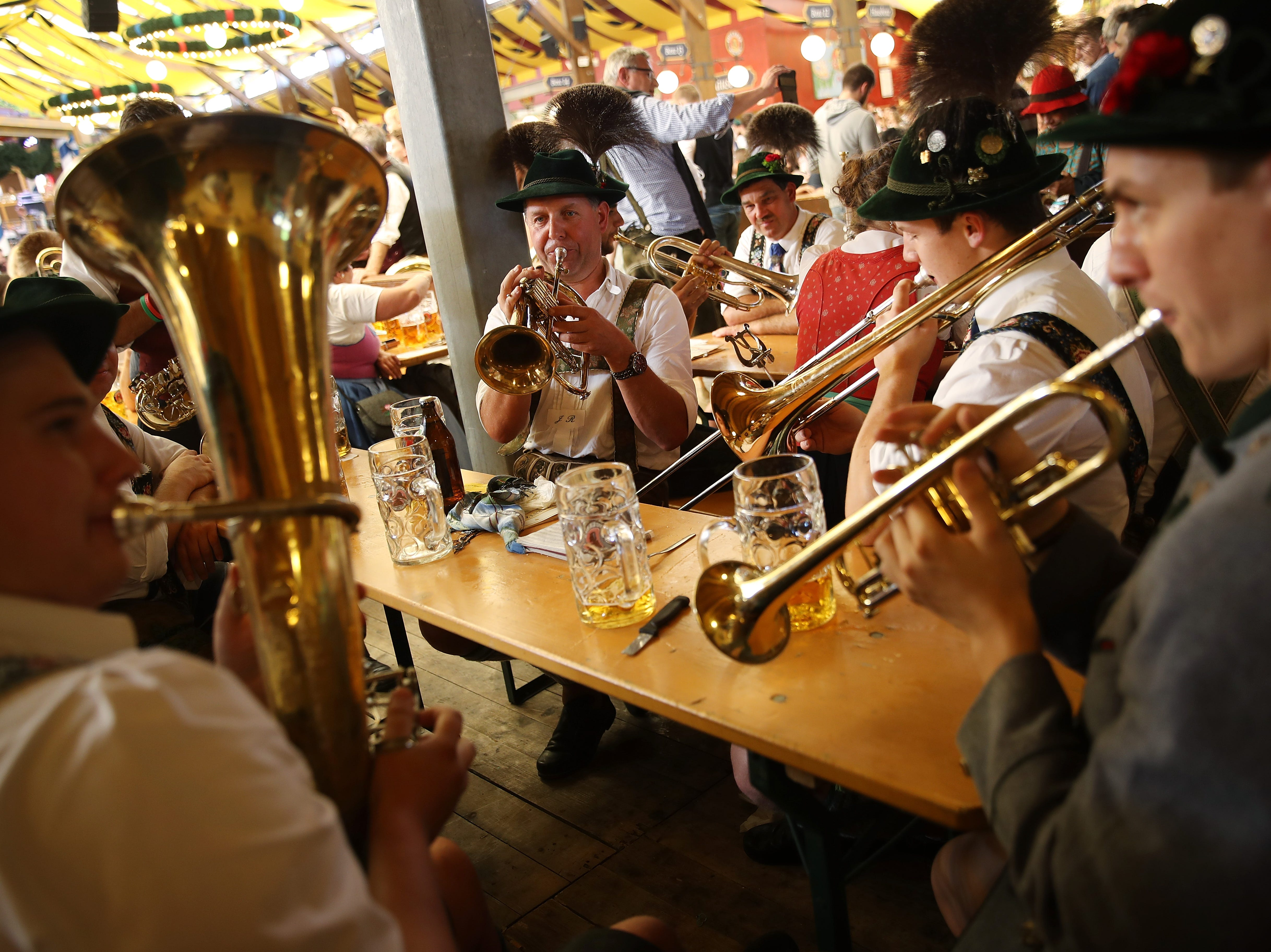 Members of a traditional Bavarian brass band play music while drinking beer in the Paulaner tent following the Oktoberfest parade of costumes of folk and crafts associations on the second day of the 2018 Oktoberfest beer festival on Sept. 23, 2018 in Munich, Germany.