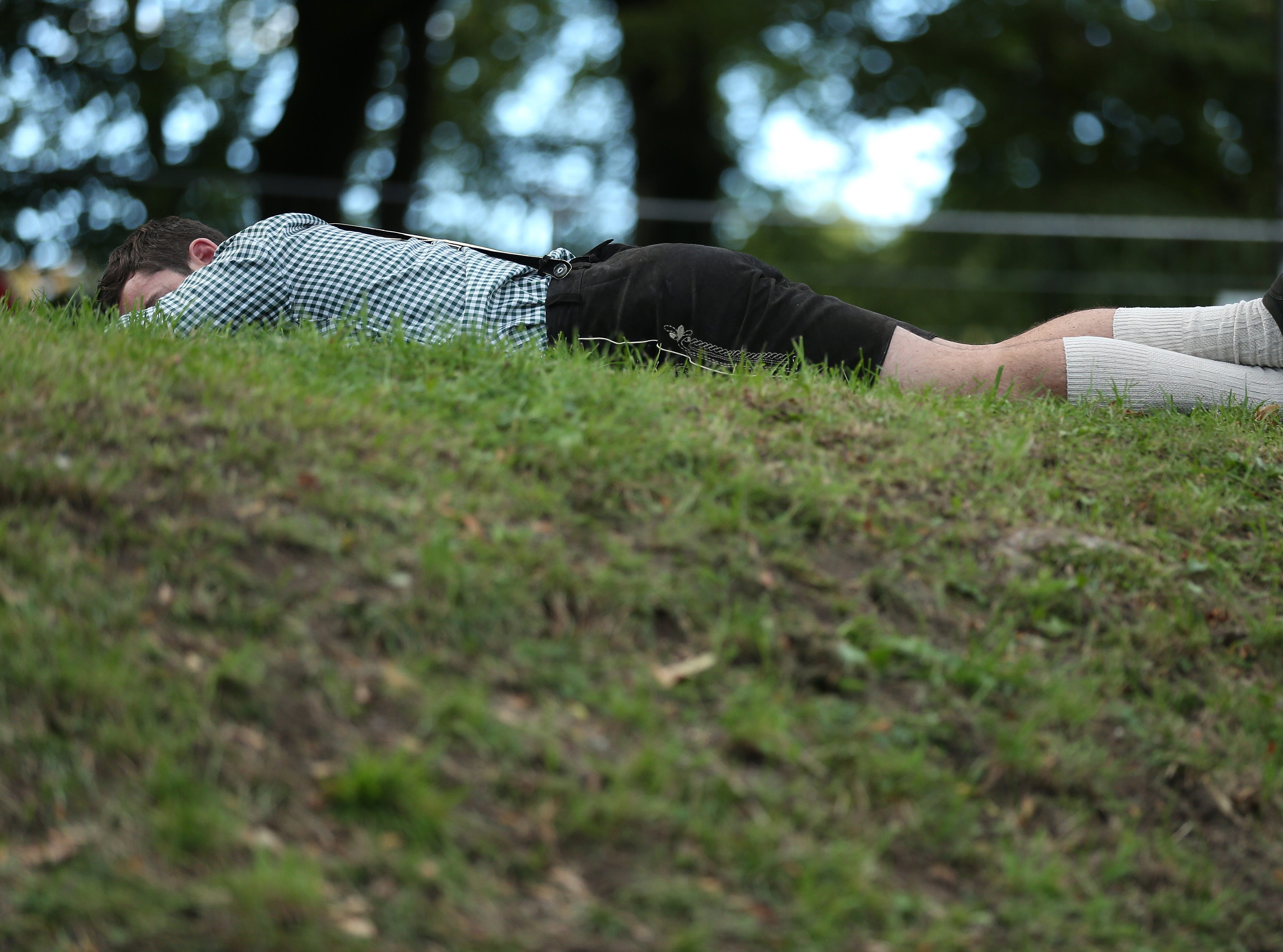=A reveler lies sleeping near beer tents on the second day of the 2018 Oktoberfest beer festival on Sept. 23, 2018 in Munich, Germany. Oktoberfest typically draws over six million visitors.