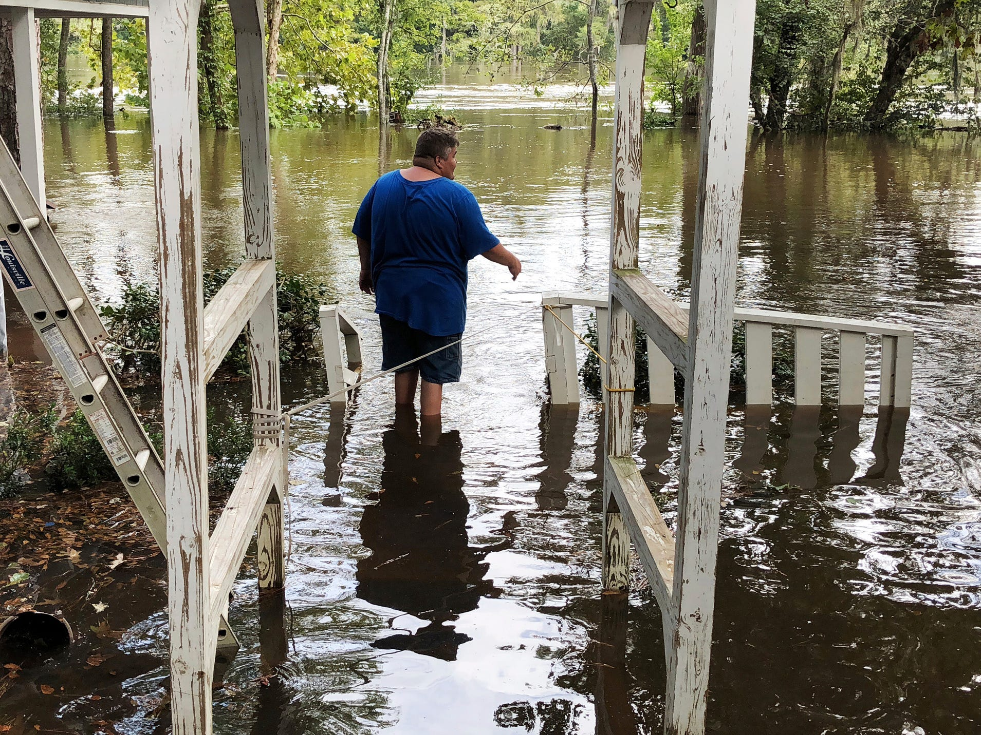 Shawn Lowrimore wades into the water near The Fellowship With Jesus Ministries church in Yauhannah, S.C., on Monday, Sept. 24, 2018. The church is on the bank of the Waccamaw River which has already risen above its record crest and is expected to keep rising for several days, forcing thousands of evacuations in the aftermath of Hurricane Florence.