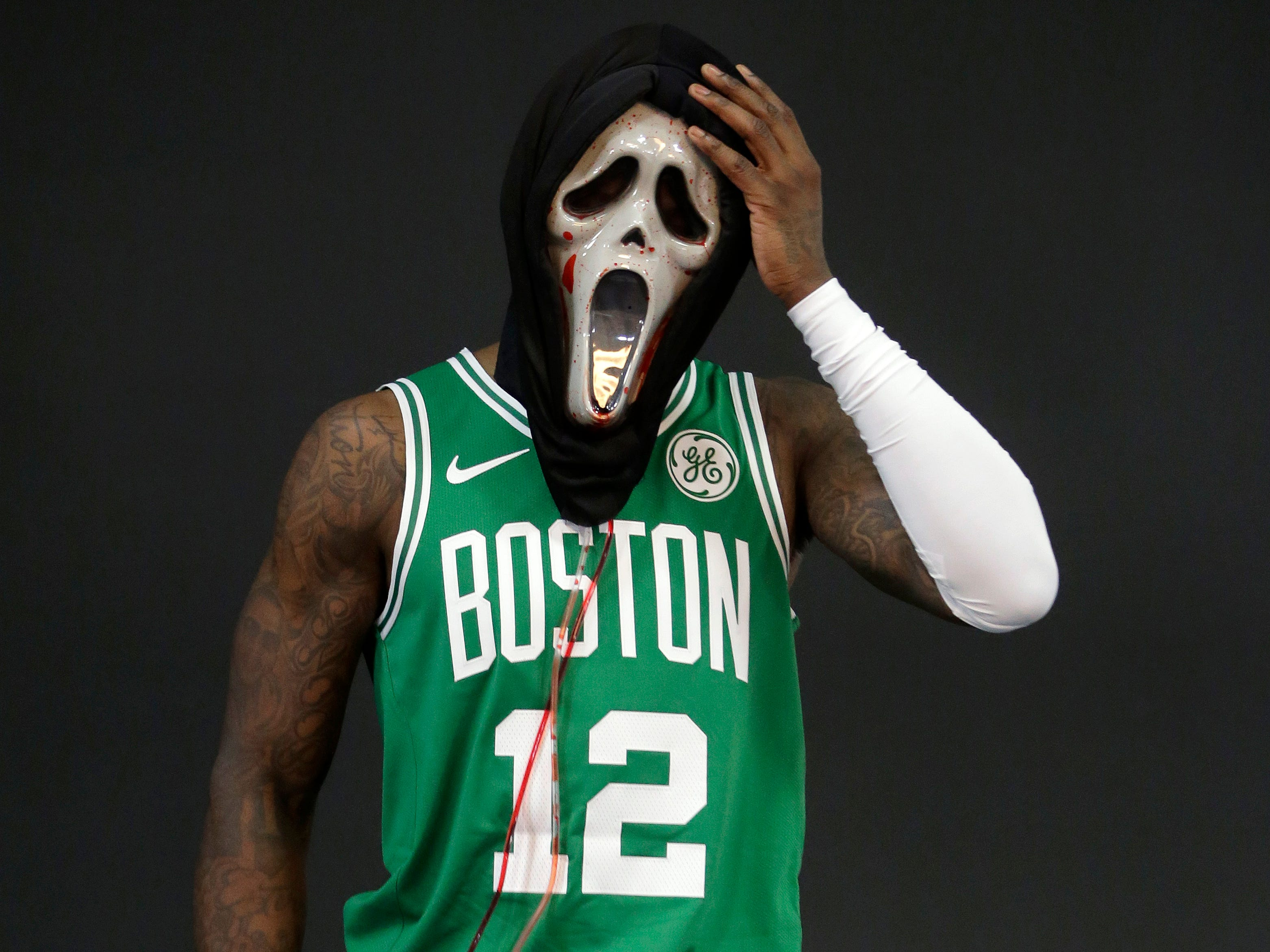 Boston Celtics guard Terry Rozier tries on a mask during a photo shoot at  media day.