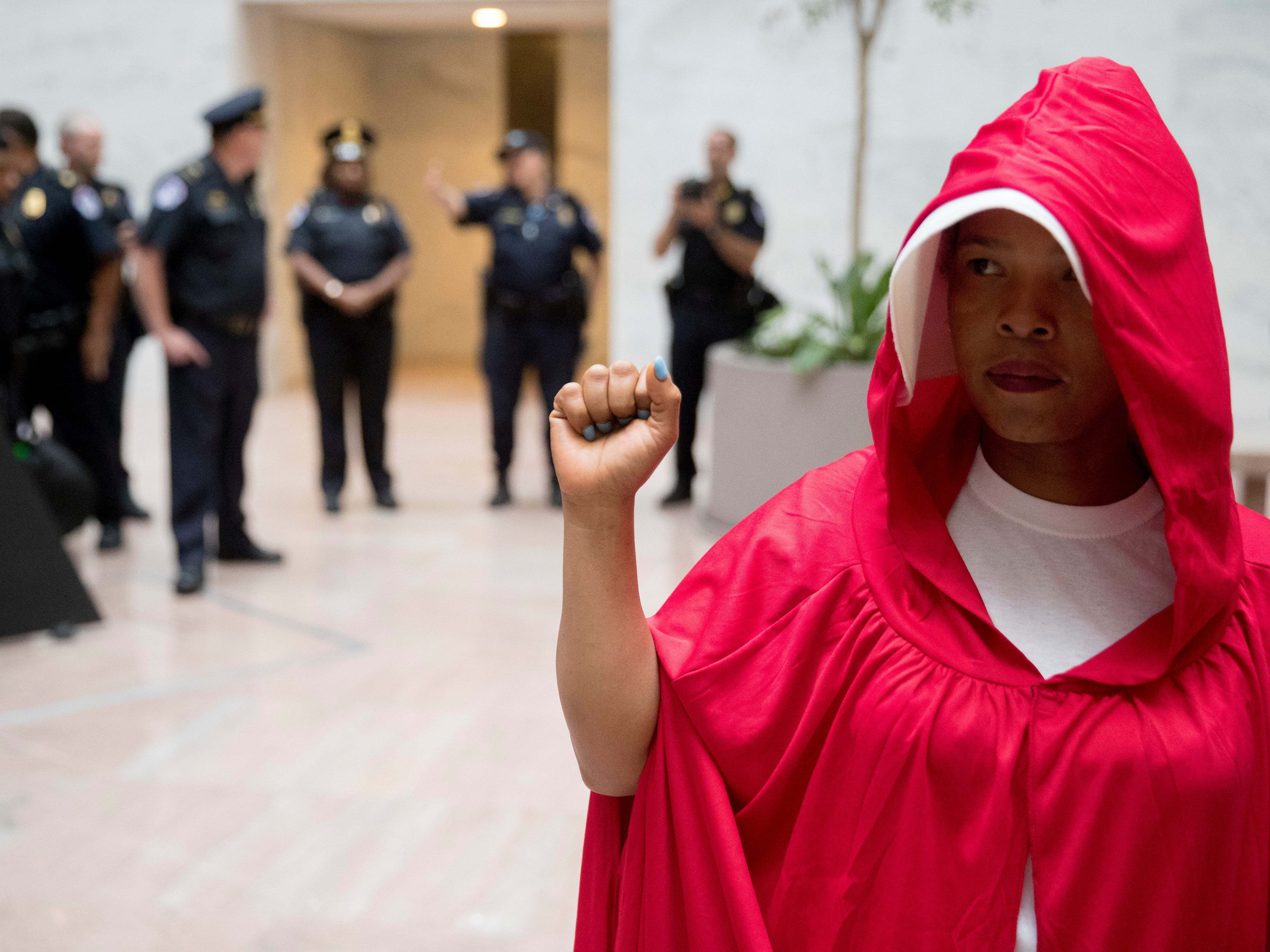 "Capitol police officers stand by and a protester of Supreme Court nominee Brett Kavanaugh wears a costume from the show ""The Handmaid's Tale,"" on Capitol Hill in Washington, Monday, Sept. 24, 2018, as the Senate begins a week of scrutiny of President Donald Trump's nominee to the high court. Judge Brett Kavanaugh's nomination to the U.S. Supreme Court has been further imperiled by a second sexual-misconduct allegation, dating to his first year at Yale University. (AP Photo/Andrew Harnik) ORG XMIT: DCAH105"