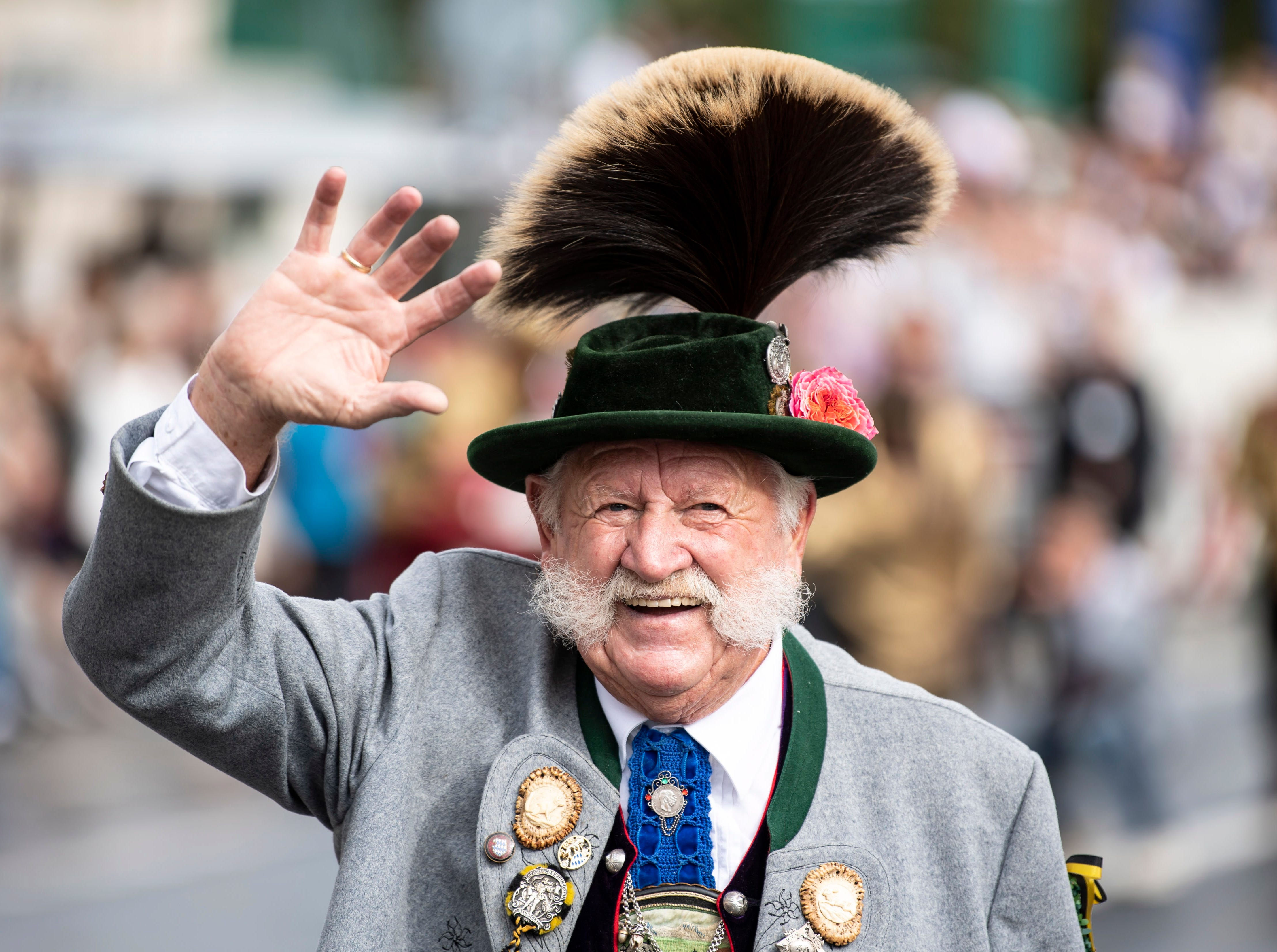 A man in traditional costume waves during the shooting club and traditional costume parade on the second day of the 185th Oktoberfest beer festival in Munich, Germany on Sept. 23, 2018.