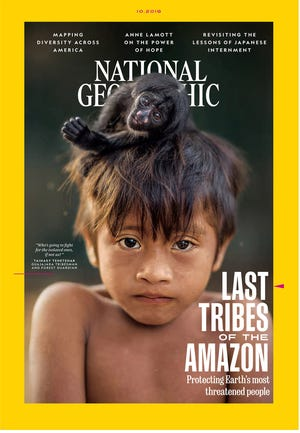 The October 2018 cover of National Geographic magazine features an image of a child living in an Amazon tribe and was taken by Charlie Hamilton James.