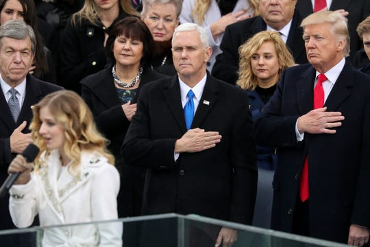 In this Jan. 20, 2017, file photo, Vice President Mike Pence and President Donald Trump listen to the singing of the national anthem by Jackie Evancho during the 58th Presidential Inauguration at the U.S. Capitol in Washington.  His daughter, Charlotte, is between Pence and Trump .