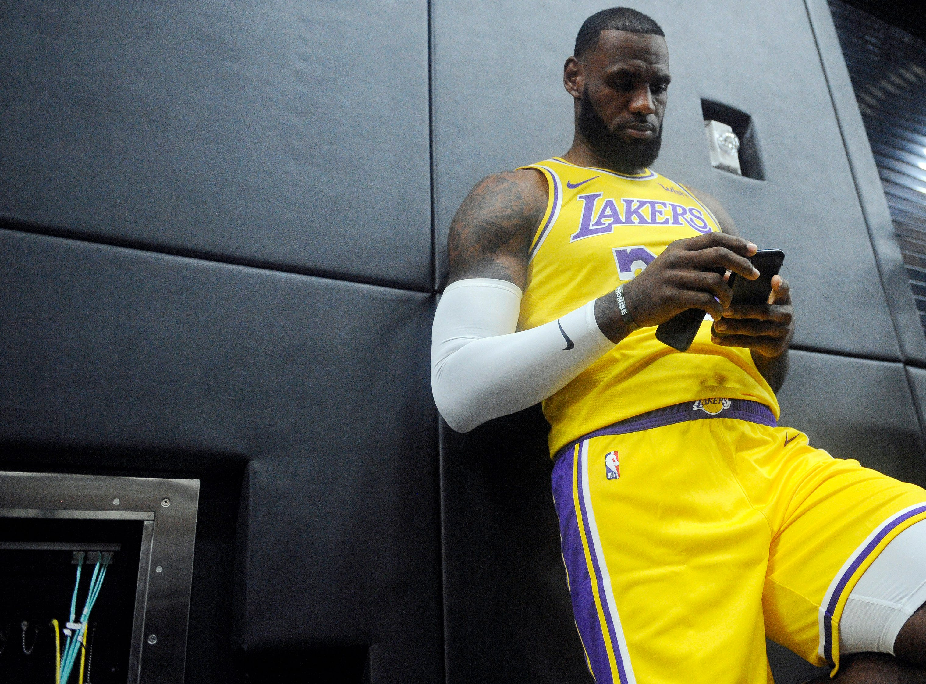LeBron James checks his cellphone before speaking to reporters in Los Angeles during NBA Media Day.