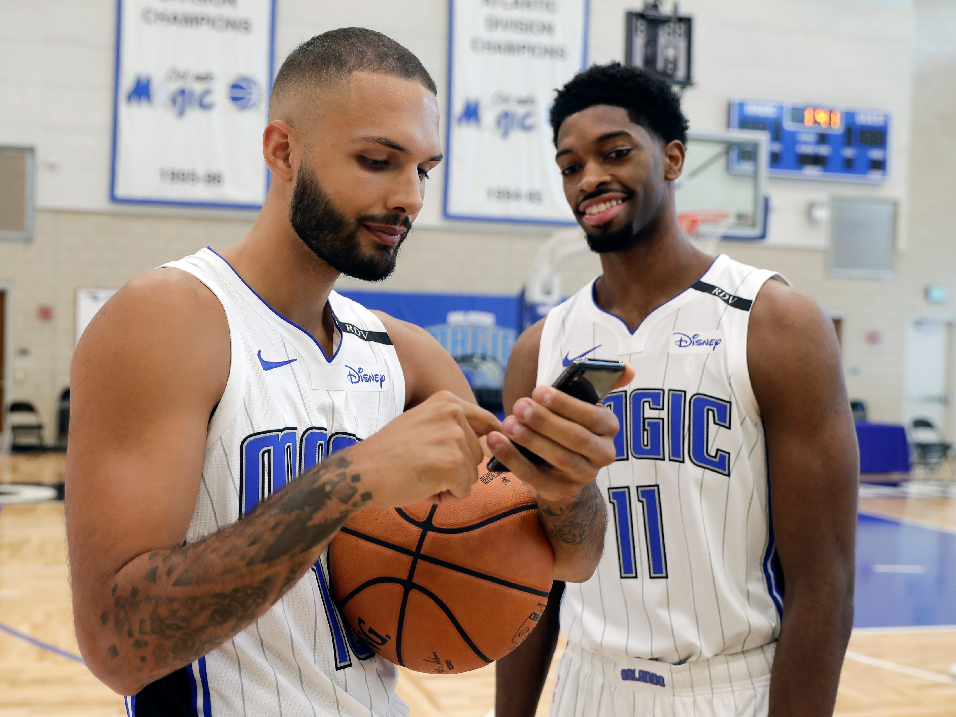 Orlando Magic's Evan Fournier, left, looks over some cell phone photos taken by teammate Amile Jefferson (11).