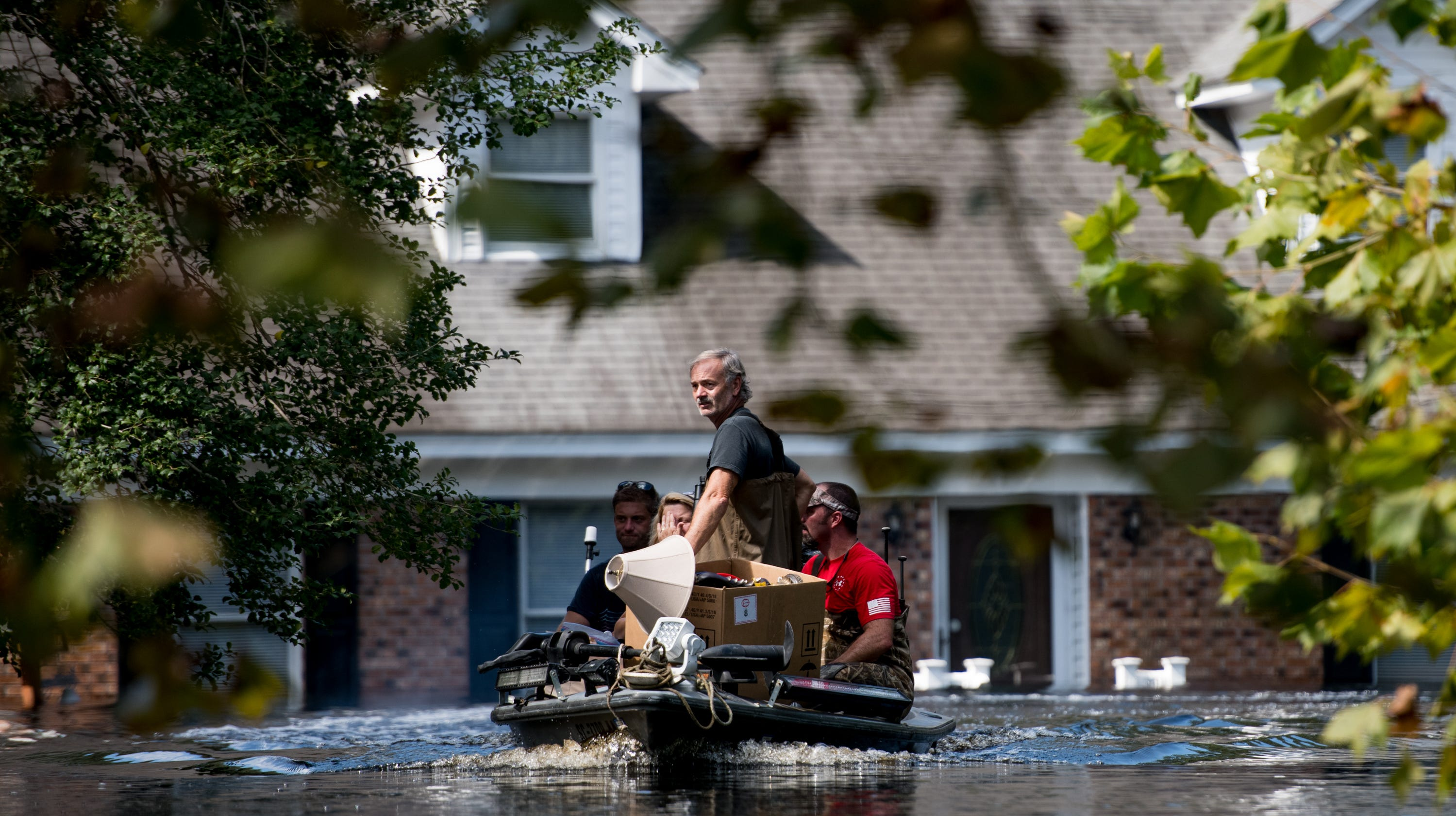 People use a boat to rescue valuables from a home inundated by floodwaters caused by Hurricane Florence near the Waccamaw River on September 23, 2018 in Conway, South Carolina.