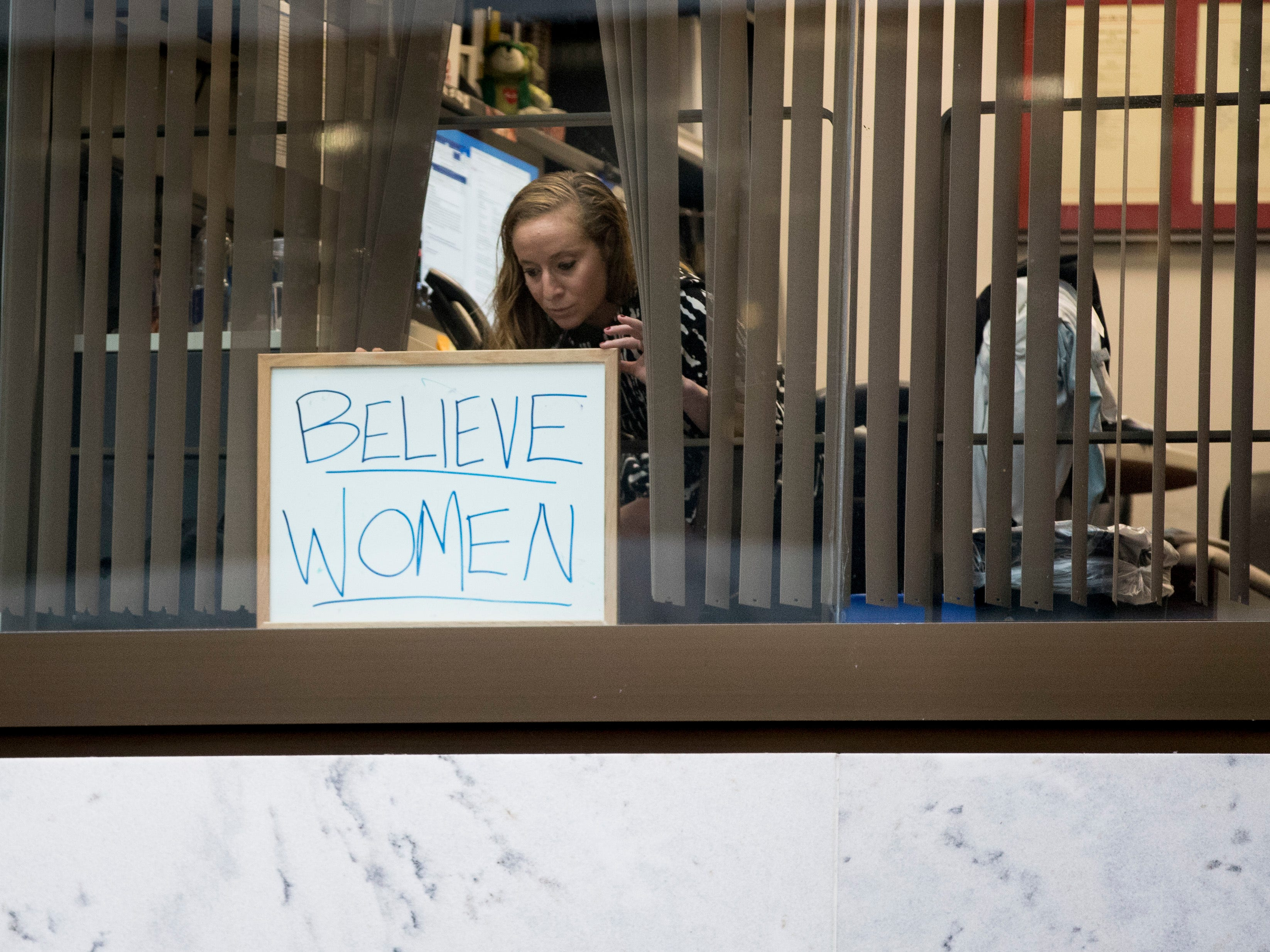 "A Capitol Hill staff member puts up a sign that reads ""Believe Women"" as she looks out her office window at a group of protesters against Supreme Court nominee Brett Kavanaugh that gathers on Capitol Hill in Washington, Monday, Sept. 24, 2018, as the Senate begins a week of scrutiny of President Donald Trump's nominee to the high court. Judge Brett Kavanaugh's nomination to the U.S. Supreme Court has been further imperiled by a second sexual-misconduct allegation, dating to his first year at Yale University. (AP Photo/Andrew Harnik) ORG XMIT: DCAH107"
